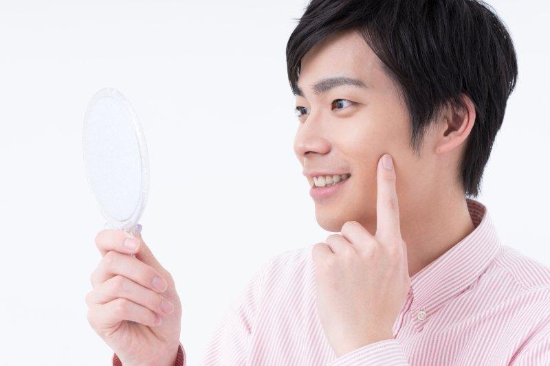 手鏡で表情を確認する男性