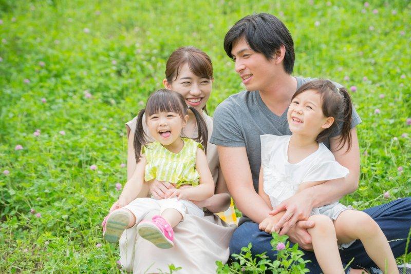 芝生に座っている4人家族