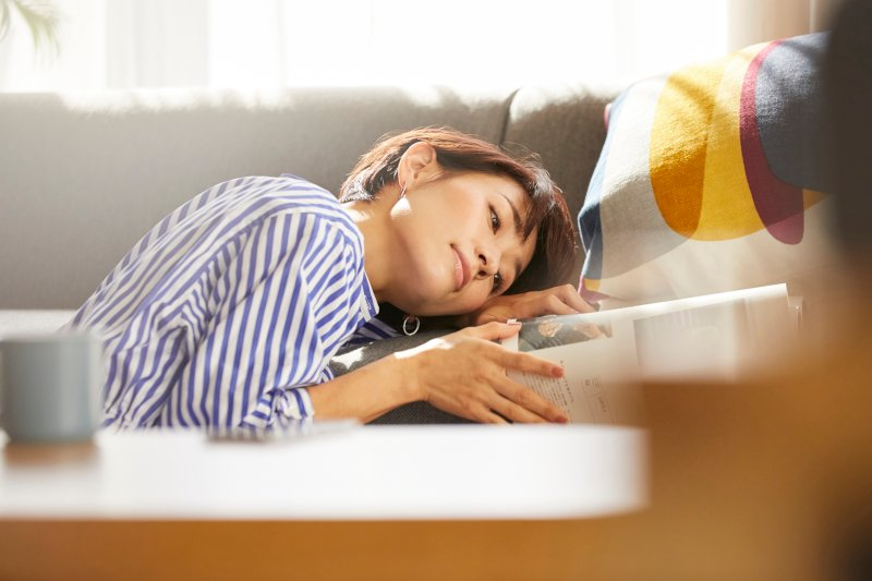 床に座って頭を横にしてソファーにつけソファ上で開いた本を見ている女性