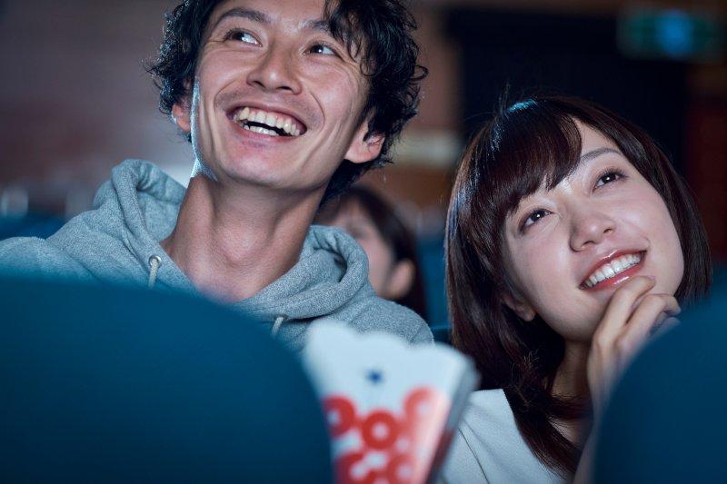 映画館で映画を見ているカップル