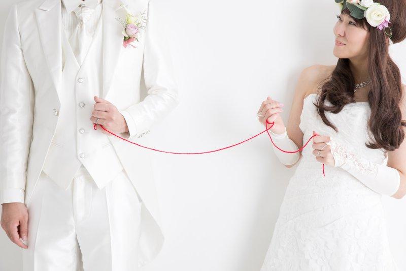 新郎新婦の小指が赤い糸で結ばれている