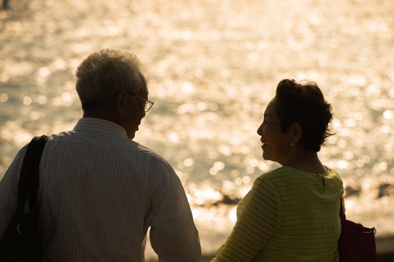 手を繋いで海辺を歩いている老夫婦の後ろ姿