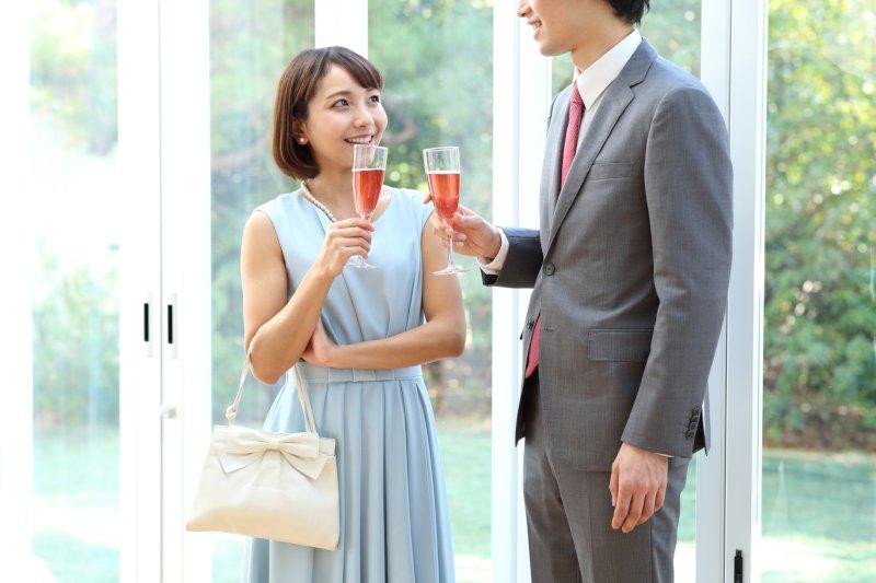 ドレスアップした男女が窓際で飲み物をもって談笑している