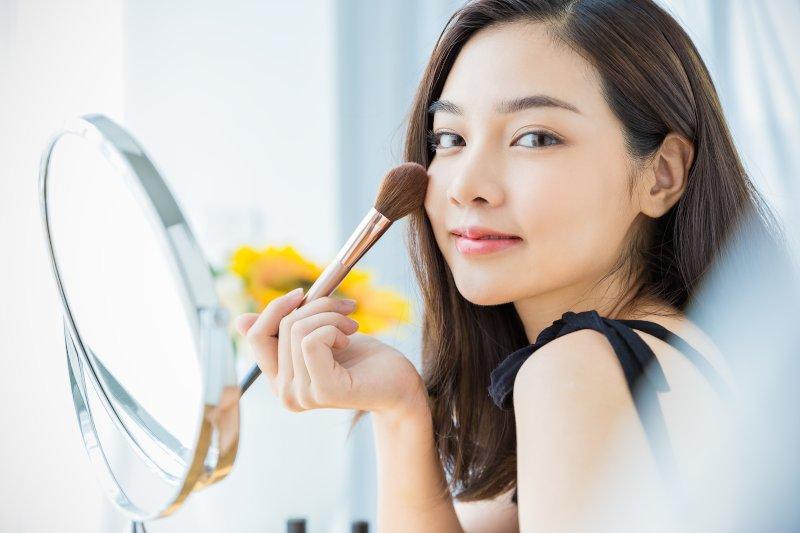 鏡の前で化粧中の女性