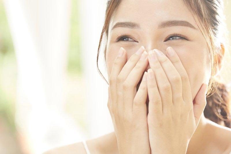 口元を隠して笑っている女性